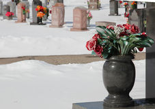 Marble vase with flowers in cemetery. A cold snowy day at the cemetery with a marble vase of flowers Royalty Free Stock Photos