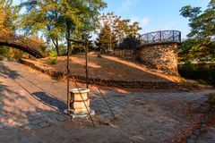 A marble well, a metal bridge and a stone lookout in the old par stock photography