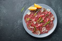 Marbled beef carpaccio with arugula, lemon and parmesan cheese on dark concrete table. Top view, flat lay with copy stock images