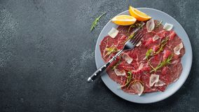 Marbled beef carpaccio with arugula, lemon and parmesan cheese on dark concrete table. Top view, flat lay with copy. Space stock images