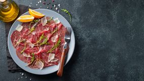 Marbled beef carpaccio with arugula, lemon and parmesan cheese on dark concrete table. Top view, flat lay with copy space royalty free stock photo