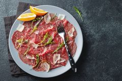 Marbled beef carpaccio with arugula, lemon and parmesan cheese on dark concrete table. Top view, flat lay with copy space stock image