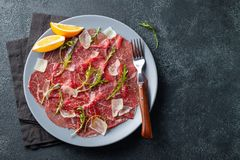 Marbled beef carpaccio with arugula, lemon and parmesan cheese on dark concrete table. Top view, flat lay with copy. Space royalty free stock photos