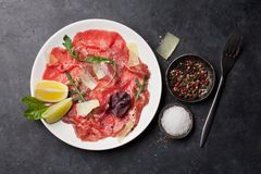 Marbled beef carpaccio. With arugula, lemon and parmesan cheese. Top view, flat lay royalty free stock photo