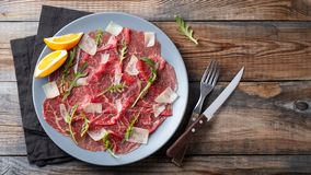 Marbled beef carpaccio with arugula, lemon and parmesan cheese on wooden table. . Top view, flat lay with copy space stock image