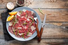 Marbled beef carpaccio with arugula, lemon and parmesan cheese on wooden table. . Top view, flat lay with copy space royalty free stock photos