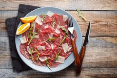 Marbled beef carpaccio with arugula, lemon and parmesan cheese on wooden table. . Top view, flat lay with copy space stock images