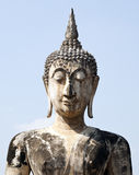 Marbled Buddha Face against Blue Sky. An ancient statue of Buddha with a marbling pattern from reconstruction on the grounds of Sukothai Historical Park in Stock Photography