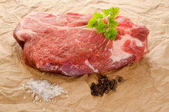 Marbled pork steak with coarse salt, pepper and parsley Royalty Free Stock Image