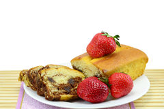 Marbled sponge cake and strawberries. Marbled sponge cake with strawberries on a plate isolated on white royalty free stock images