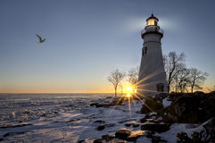 Marblehead Lighthouse Sunrise. The historic Marblehead Lighthouse in Northwest Ohio sits along the rocky shores of the frozen Lake Erie. Seen here in winter with Stock Photo