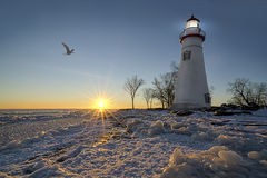Marblehead Lighthouse Sunrise. The historic Marblehead Lighthouse in Northwest Ohio sits along the rocky shores of the frozen Lake Erie. Seen here in winter with Royalty Free Stock Photography