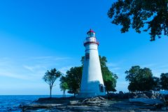 Marblehead lighthouse with waves crashing the rocks royalty free stock photography