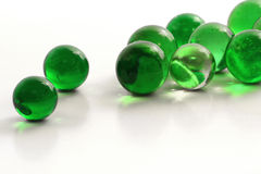 Marbles. Green glass marbles on white Royalty Free Stock Photos