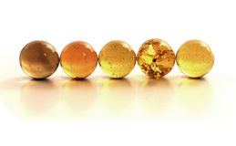 Marbles. Golden glass marbles in a row Stock Image