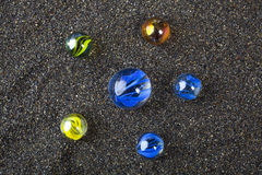 Marbles. 6 marbles on black sand Royalty Free Stock Photos