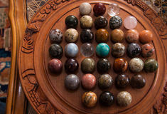 Marbles board game. On a circular wooden board Royalty Free Stock Photos