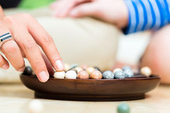 Marbles in a dish. Young Indonesian couple - men and women - at home playing with marbles Stock Photo
