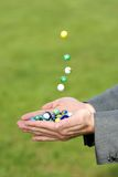 Marbles dropping into a hand outdoors Stock Image