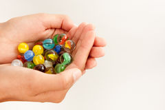 Marbles in Hands. Hands cupped holding colorful glass marbles Stock Images