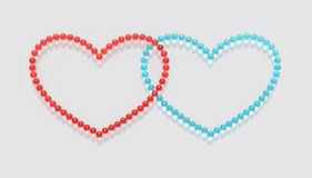 Marbles Heart A1. Clear, shining blue and red marbles are arranged on a white background in two overlapping heart shapes, expressing playful love and sharing Stock Photos