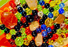 Marbles and pebbles. Array of colored glass marbles and pebbles Royalty Free Stock Photos