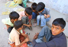 Marbles. Street scene from New Delhi, India with group of children playing marbles