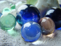 Marbles on towel close up. Close up photo of colorful glass marbles on white towel Royalty Free Stock Images