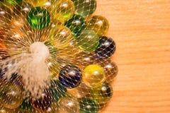 Marbres en verre colorés dans le filet Images libres de droits