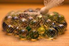 Marbres en verre colorés dans le filet Image libre de droits