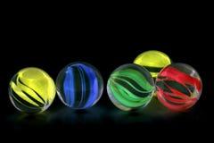 Marbres en verre colorés sur le fond noir Image stock