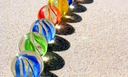 Marbres en verre colorés sur le sable Photo libre de droits