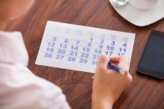 Marcação da mulher de negócios no calendário fotos de stock