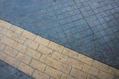 A marcação de estrada amarela alinha sobre no pavimento cinzento da pedra Foto de Stock