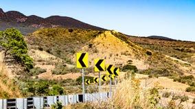 Marcação de estrada na estrada, curva perigosa com uma barreira do metal e um fundo à terra árido imagens de stock royalty free