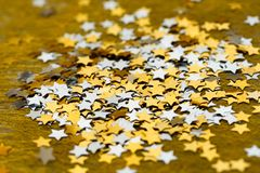 Marca con asterisco la Navidad brillante dispersada en un fondo del oro Imagen de archivo