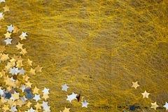 Marca con asterisco la Navidad brillante dispersada en un fondo del oro Fotografía de archivo libre de regalías