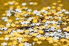 Marca con asterisco la Navidad brillante dispersada en un fondo del oro Fotografía de archivo