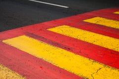 Marca de camino del paso de peatones con las líneas amarillas y rojas imagenes de archivo