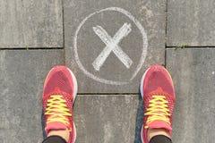 Marca de cotejo ninguna muestra en la acera gris con las piernas de la mujer en zapatillas de deporte, visión superior imágenes de archivo libres de regalías