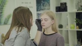 Marca de la ceja para la chica joven que colorea almacen de metraje de vídeo