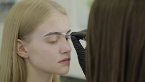 Marca de la ceja para la chica joven que colorea metrajes