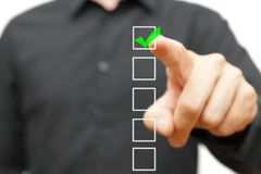 Marca de verificação nova do homem de negócios na lista de verificação com marcador Fotografia de Stock