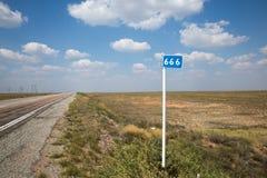Marca del kilómetro de tres sixes en fondo del camino del verano y del cielo nublado Fotos de archivo libres de regalías