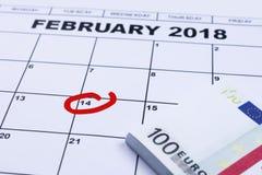 Marcado 14 de febrero en el calendario y el dinero puestos a un lado para los regalos Imagen de archivo libre de regalías