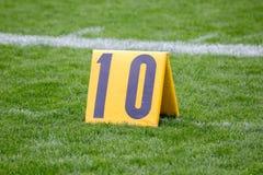 Marcador de jarda do futebol americano 10 na grama pela linha fotos de stock