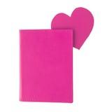 Marcador de papel roxo do coração dentro de um livro roxo isolado no branco fotografia de stock
