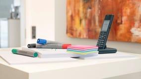 Marcador de Whiteboard y notas pegajosas coloreadas delante de una pintura moderna fotografía de archivo libre de regalías