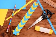 Marcador do papel amarelo e azul As tesouras, vara da colagem, papel colorido cobrem, a régua, lápis em uma tabela de madeira Art Foto de Stock