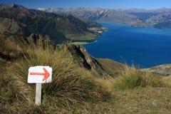 Marcador rojo de la flecha que muestra la dirección sobre el lago Hawea Imagenes de archivo
